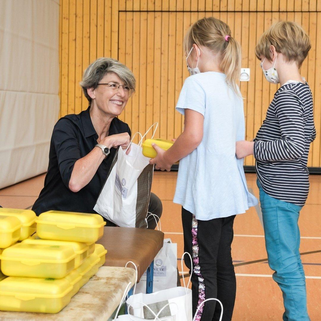 Judith Moog übergibt Bio-Brotboxen an Erstklässler